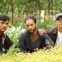 Three brothers pose in front of their carefully maintained flower gardens