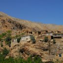 Settlements cling to cliffs near the treeline of the Hindukush Mountains