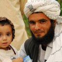 A proud and smiling Pashtun tribesman poses with his little daughter