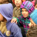 Children line up in the cold to get food and clothing in a donation center