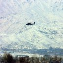 In the distance, an American Apache attack helicopter patrols the huge, white blanketed mountains