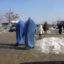 Two burka clad women hurry along a rural road. Although not mandatory anymore, many rural women still wear this all encompassing cloak