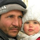 Anxiety, maybe resignation to his situation reflect in this dad's face, as he holds his innocent child tightly