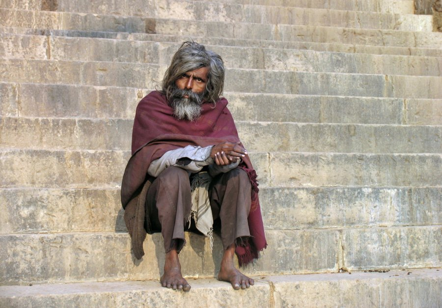 Man sitting on edge of Ganges River in Varanasi India