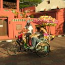 A highly decorated bicycle takes patrons on a cruise through the old town of Malacca