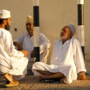 Men with traditional Omani tunics and hats gather for an early morning chat