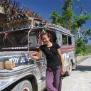 Woman standing next to Philippines famed Jeepneys