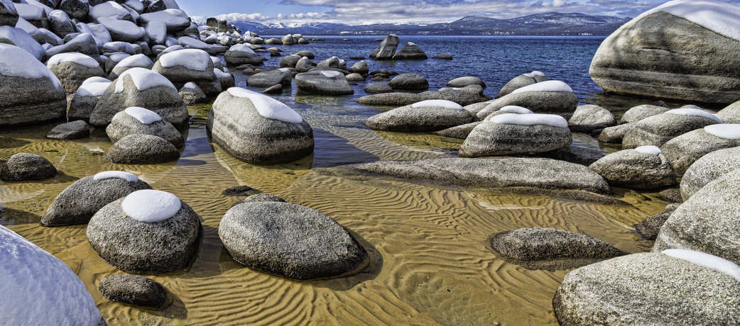 Snow-covered boulders and sandy lake bottoms of Sand Harbor Lake Tahoe, USA.