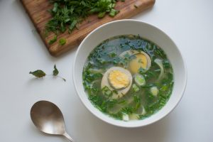 Summer green soup - bouillon with noodles, egg and spring onion - on white background