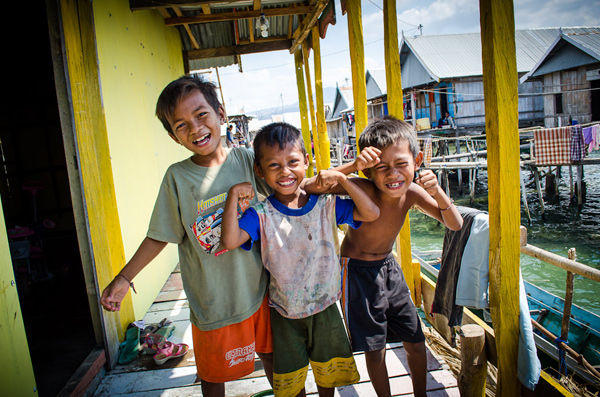 Three little boys posing for a photo in a fishing village in Maumere, Flores, Indonesia