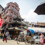 A rickshaw driving through an intersection in Kathmandu, Nepal