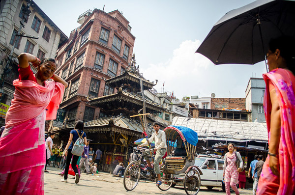 A rickshaw driving through an intersection in Kathmandu, Nepal