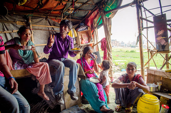 A family inside their tent home in Kathmandu, Nepal