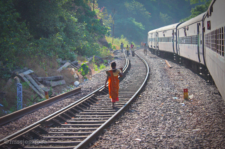 En route to Hampi, women construction workers walk along the train track