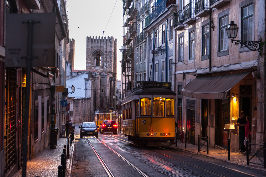 Tram crossing street at evening in Lisbon, Portugal