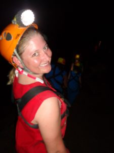 Girl with headlamp on in cave