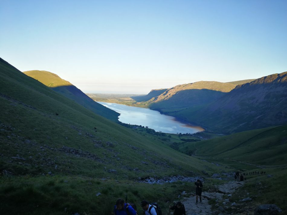 Looking back towards Wast Water as the sun rises hiking up Scafell Pike