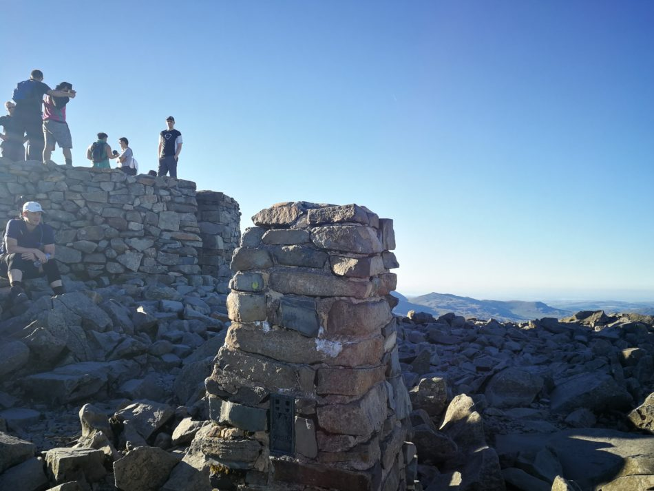 Busy summit cairn at the top of Scafell Pike