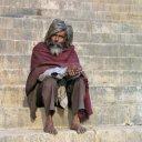 Man sitting on edge of Ganges River in Varanasi India