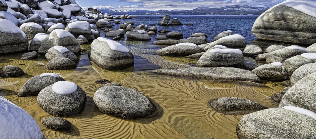 Snow-covered boulders and sandy lake bottoms of Sand Harbor Lake Tahoe, USA.