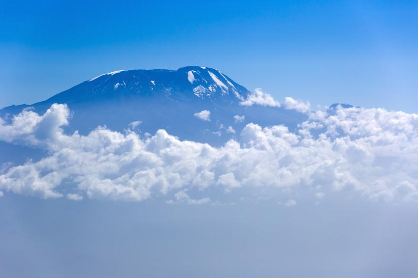 View of Mount Kilimanjaro from Mt Meru, Tanzania in Africa. Clouds surrounding the mountain.