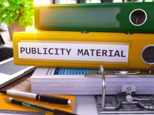 Publicity Material on Yellow Ring Binder. Blurred, Toned Image.