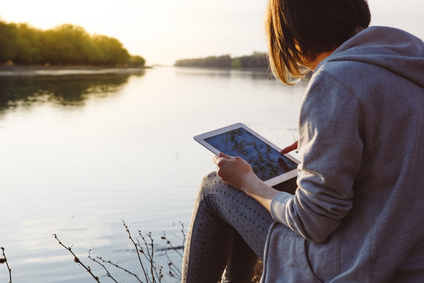 girl working with tablet at the river