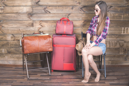 Young woman already packed her things, clothes at luggage, suitcase