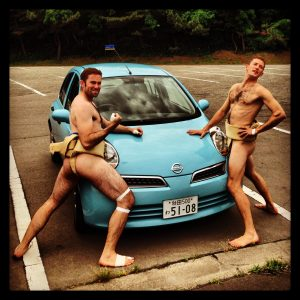 Proud sumo wrestlers getting ready to destroy a small vehicle